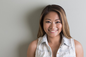 Asian woman standing on grey background