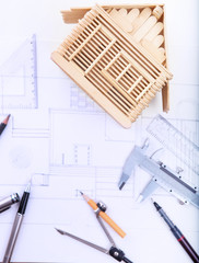 architect working table with plan home model and writing instrum