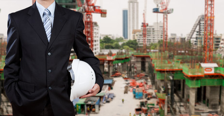 Businessman holding safety helmet with construction site in back