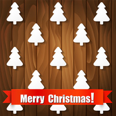 Christmas card with trees on wooden background