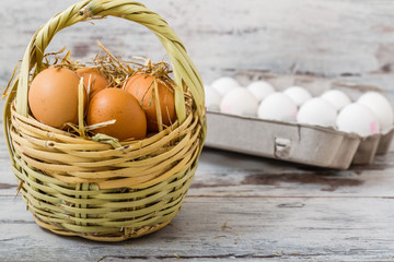 Eggs in Straw Basket and Modern Cardboard