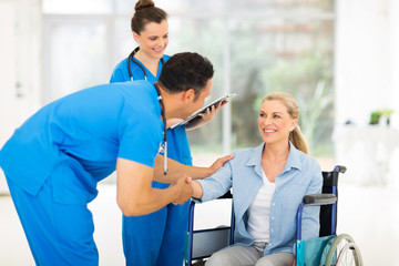 male doctor greeting handicapped patient