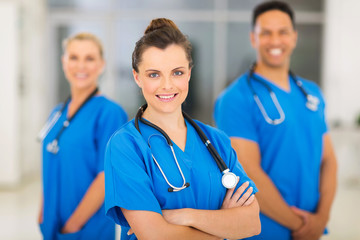 young female nurse with colleagues on background