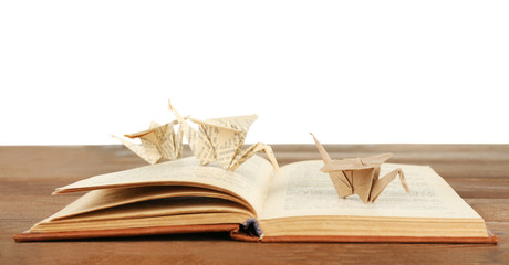 Origami cranes on old book on wooden table, on white background