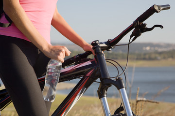 Cyclist woman with bottle of water