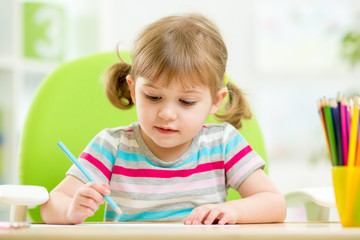 cute little girl drawing with colourful pencils