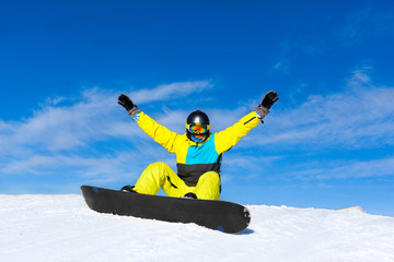 snowboarder excited happy raised arms hands up sitting on snow