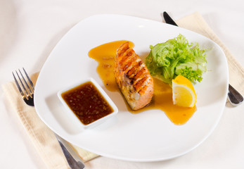 Grilled Salmon Dish with Sauce and Garnish
