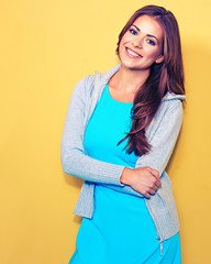 Casual stule dressed young woman standing against yellow.