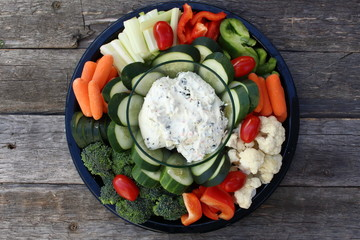 Plate of raw vegetables and dip on old wooden planks