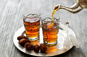 Traditional arabic tea with dates and sugar on a plate