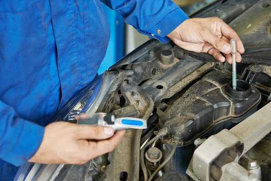 auto mechanic tests car antifreeze liquid