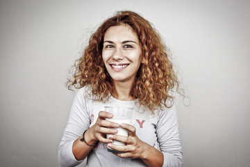 happy young woman with milk over grey background