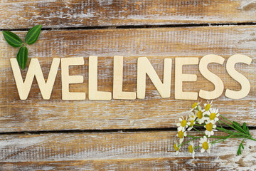 Wellness written with wooden letters, chamomile flowers on wood Fototapete