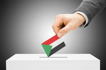 Voting concept - Male inserting flag into ballot box - Sudan