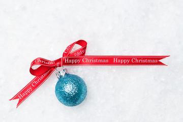 Weihnachtskugel im Schnee mit Schleifenband