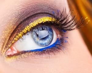 Macro photo of blue eye looking away. Professional make up on ey