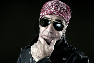 Pensive biker with leather jacket, sunglasses and bandana