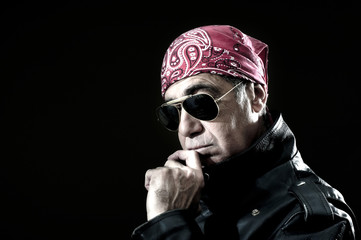 Pensive biker with leather jacket, sunglasses and bandana