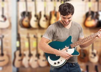 Foto auf AluDibond Musikladen Man testing a guitar in a store