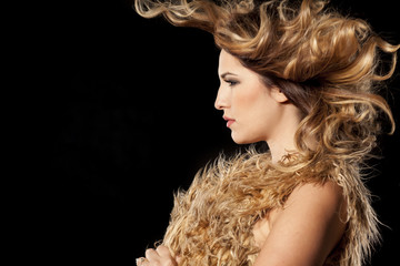 beautiful young woman with wind in her hair on a black