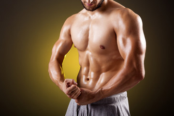 Fit man with beautiful torso posing on dark background