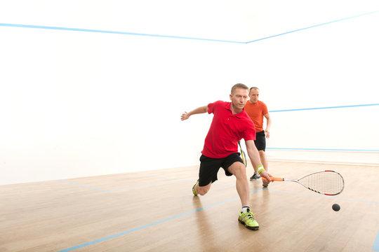 Two men playing match of squash.