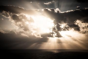 Dramatic sunset rays through a cloudy dark sky over the ocean