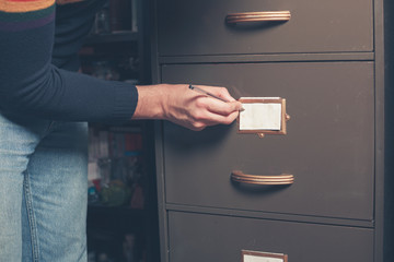 Man writing note on file cabinet
