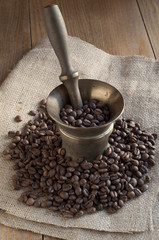 Coffee beans on sackcloth and bronze mortar.