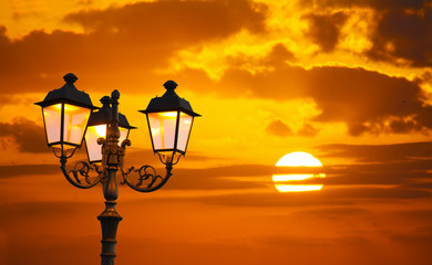 Fotobehang - orange sky with a shining sun and a lamppost