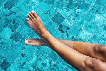 Bare Woman Legs Relaxing on Clear Water