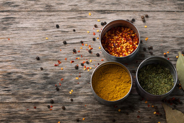 Overhead view of Colourful dried ground spices in bowls on old a