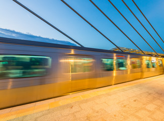 Train speeding up on a station at night. Blurred motion effect