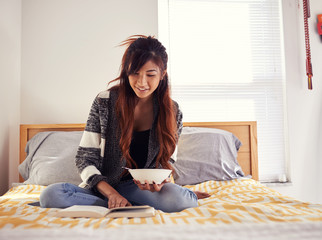 happy asian teen girl reading book and eating soup