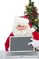 Santa claus showing his laptop