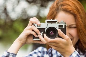 Pretty redhead taking a picture with retro camera