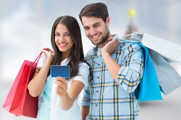 Composite image of couple with shopping bags and credit card