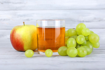 glass of juice with fresh grape and apple on grey wooden table