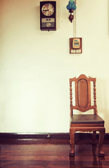 Antique wood chair and clock on wooden floor in vintage style