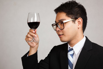 Asian businessman look at  red wine