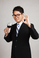 Asian businessman show OK with glass of red wine