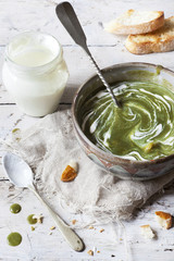 peas and spinach cream soup with sour cream on bowl