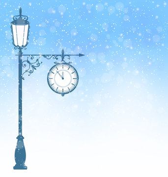 Vintage winter lamppost with clock in snowfall on blue backgroun