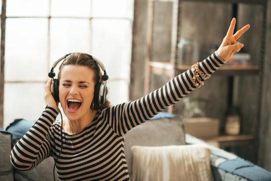 Cheerful young woman listening music in headphones