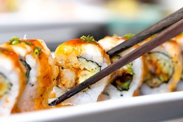 Sushi roll with black chopsticks