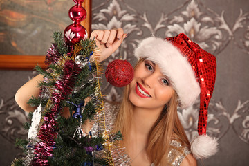 Beautiful woman decorating the Christmas tree