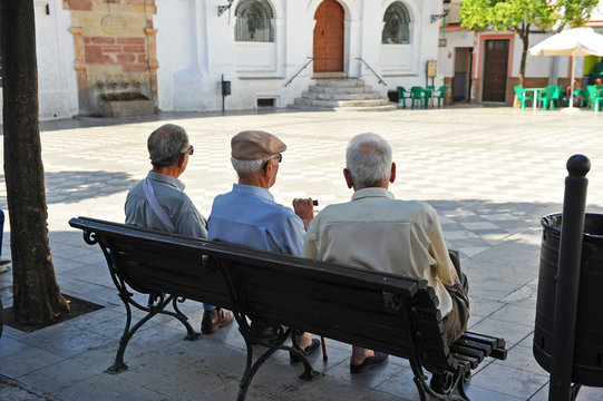 Three old men sitting on the bench, Spanish village