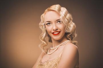 Vintage portrait of a girl in a gold dress. Blonde in studio.