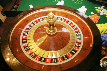 Roulette wheel with green gaming table